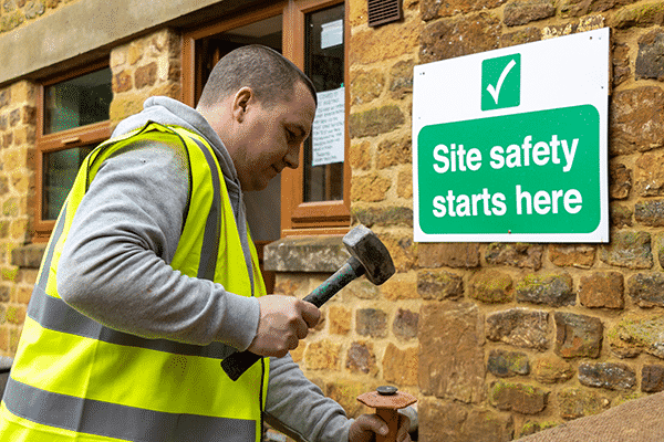 ashby facilities care home construction worker with a hammer in front of safety sign